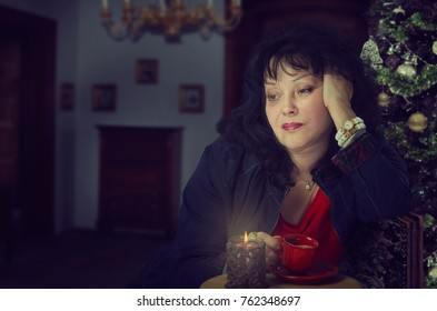 Mature woman is sad because she is alone at Christmas Eve. Woman drinks coffee, her head is propped up with hand. Dark blurred indoors background with decorated tree
