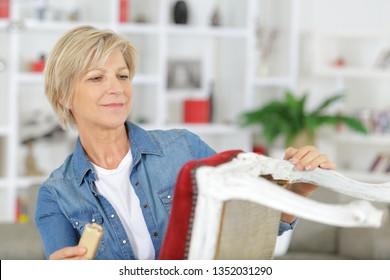 mature woman sanding down chair legs