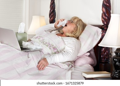 Mature woman self-isolating and trying to work from home as she lies in bed and sneezes