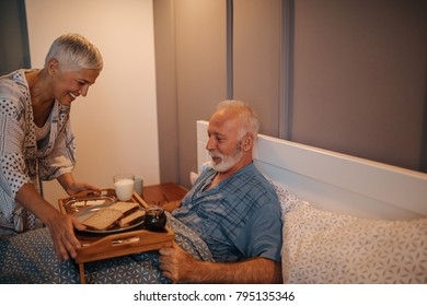 Mature woman serving breakfast in bed to her husband