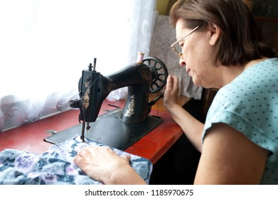 Mature woman sewing with old machine