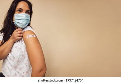 Mature woman shows a bandage she received after getting a vaccination during covid-19 immunization program. Woman wearing protective face mask received a coronavirus vaccine on her arm.