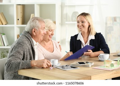 Mature woman signing a a mortgage loan agreement in office of real estate agent