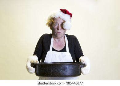 Mature woman with singed face holding roasting pan with santa hat and apron.