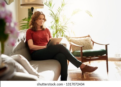 Mature woman sitting alone on a sofa in her sunny home browsing the internet with a digital tablet