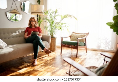 Mature woman sitting alone on a couch in her sunny apartment using a digital tablet to browse online