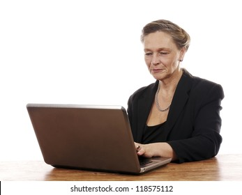 Mature woman sitting by table working on notebook computer isolated on white background