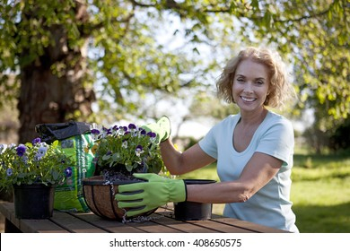 A mature woman sitting at a garden bench planting hanging baskets