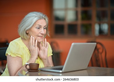 Mature woman sitting with laptop in hotel with tea