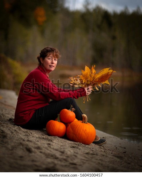 Mature woman sitting on the beach beside a lake holding orange colored leaves beside several pumpkins.