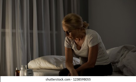 Mature woman sitting on bed, suffering from depression, pills on table, problem