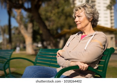 Mature woman sitting on a bench in a park