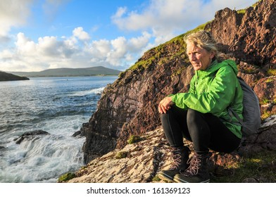 mature woman sitting on cliff above Dingle Bay looking for Fungie, Dingles world famous Dolphin