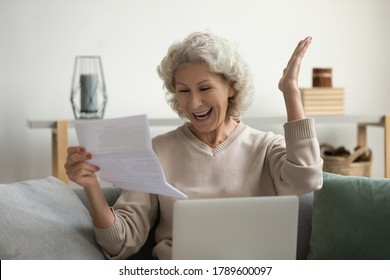 Mature woman sitting on couch holding sheets read official paper event invitation letter feels overjoyed. Happy mature female put notebook on laps excited by incredible great fantastic news from bank