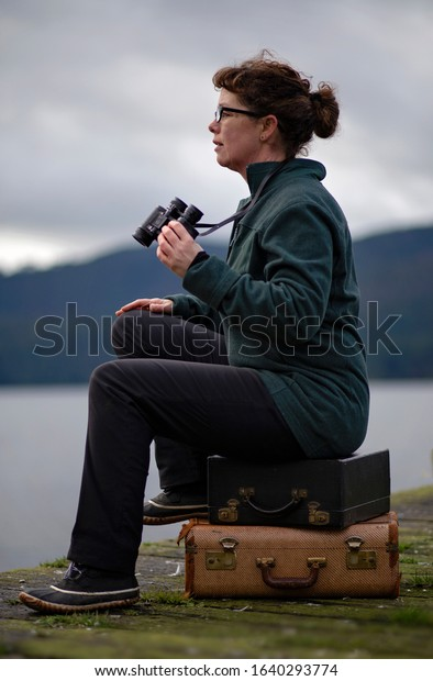 Mature woman sitting on a dock holding binoculars.