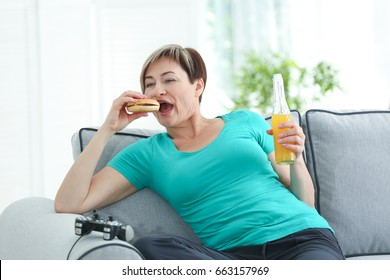 Mature woman sitting on sofa with hamburger, soda and videogame console. Sedentary lifestyle concept