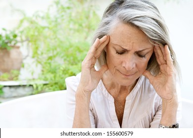 Mature woman sitting on a white sofa in a home garden touching her head with her hands while having a headache pain and feeling unwell, outdoors.