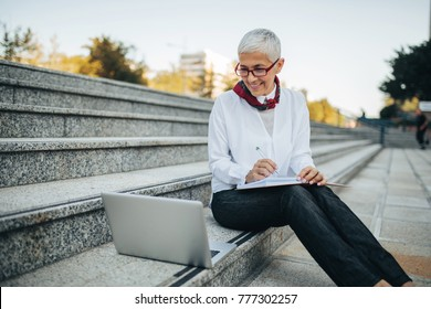 Mature woman sitting outdoors using a computer