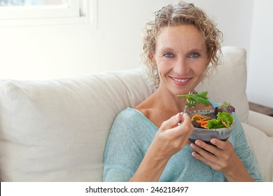 Mature woman sitting and relaxing on a white couch at home while eating a small green salad, home interior. Senior woman eating healthy food. Well being indoors. Lifestyle, smiling.