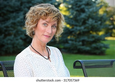 Mature woman sitting relaxing outside on patio