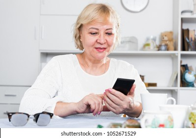 Mature woman sitting at table at home and looking at smartphone in her hands