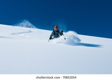 mature woman skiing un-tracked deep powder snow on bluebird day in aspen back-country