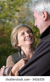 Mature woman smiles to her man, focus on woman.
