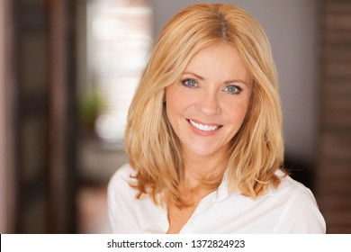Mature woman smiling at the camera. She relaxing at home. Beautiful