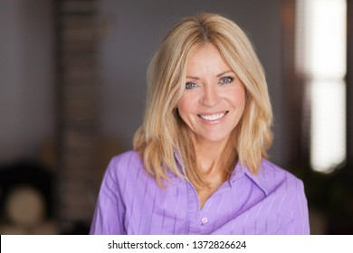 Mature woman smiling at the camera. She relaxing at home