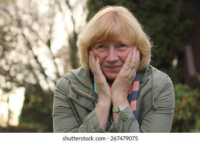 Mature woman smiling in genuine amusement. Mental health concept.