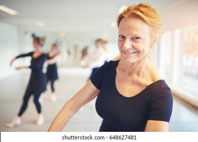 Mature woman smiling and looking at camera while performing ballet in the class.