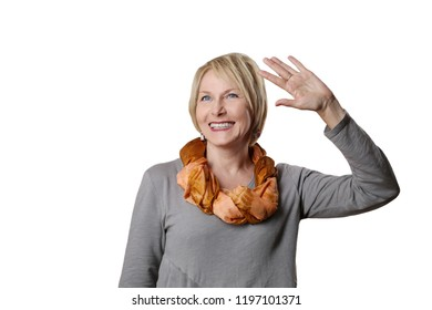 Mature woman smiling welcomes with raised hand isolated on white background