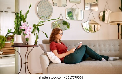 Mature woman smiling while laying on her living room sofa at home browsing the internet with a digital tablet