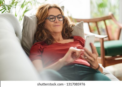 Mature woman smiling while lying on her living room sofa at home reading a text message on her cellphone