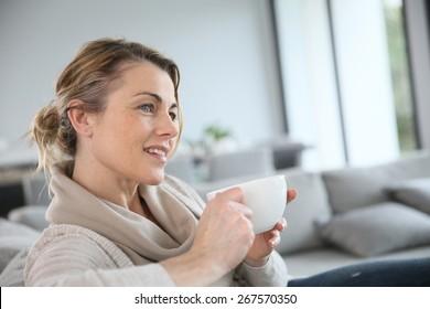 Mature woman in sofa drinking hot coffee