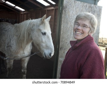 Mature woman spending time with her horses in their stable