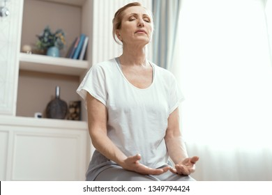 Mature Woman In Sportwear Meditating At Home. Practises Yoga. Sitting With Closed Eyes On Yoga Mat. Yoga Concept.