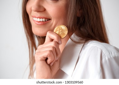 Mature woman standing isolated on white wall holding eletronic cash smiling cheerful close-up