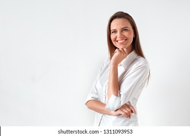 Mature woman standing isolated on white wall looking forward smiling cheerful