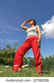 mature woman is standing on a meadow outside in summer and looks around, Preparing for sporting activities