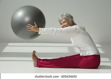 Mature woman stretching with exercise ball.