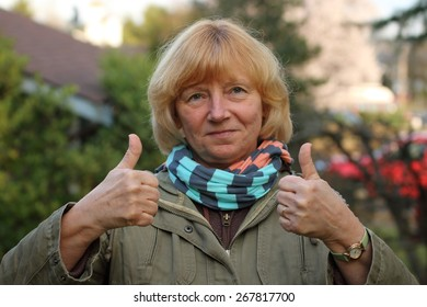 Mature woman in the suburbs with a smile and making a two thumbs up sign.