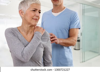 Mature Woman suffering from back pain during medical exam. Chiropractic, osteopathy, Physiotherapy. Alternative medicine, pain relief concept.