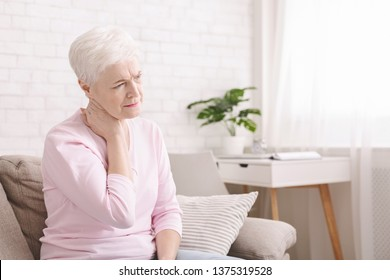 Mature woman suffering from backache at home, massaging neck with hand, feeling exhausted, empty space