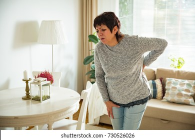 Mature woman suffering from backache at home. Massaging lower back with hand, feeling exhausted, standing in living room.