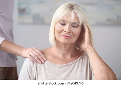 Mature woman suffering from headache while young woman holding hand on her shoulder indoors. Elderly care concept
