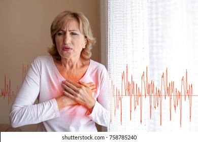Mature woman suffering from heart attack at home