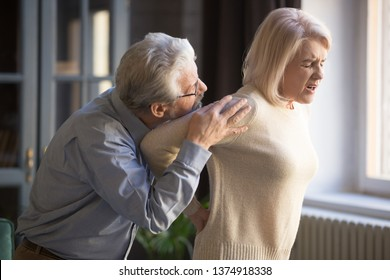 Mature woman suffering from sudden backache, feeling pain in back, old grey haired man, husband embracing, supporting unhappy wife, health problem concept, middle aged couple, family at home