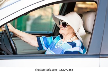 mature woman in sunglasses driving automobile .