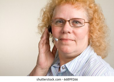 A mature woman taking a call on a hands free telephone headset